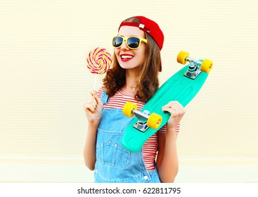 Fashion portrait pretty cool smiling girl with a lollipop and skateboard over white background