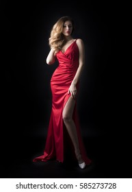 Fashion portrait of pretty sexy young blonde woman in red dress posing isolated on black background