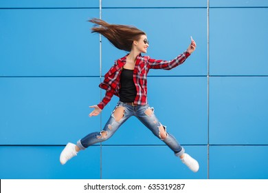 Fashion portrait of pretty smiling and jumping woman in sunglasses with smartphone against the colorful blue wall. Copyspace. Flying hairs
