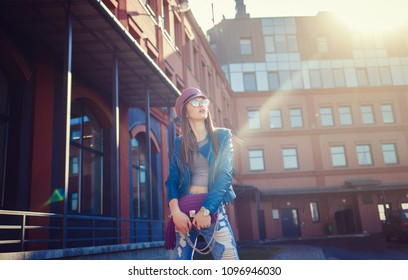 Fashion portrait pretty sweet young woman wearing leather jacket and sunglasses over urban background