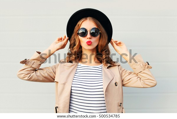 Fashion portrait pretty sweet young woman blowing red lips wearing a black hat sunglasses coat over grey background