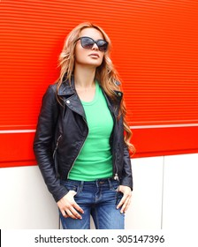 Fashion portrait pretty woman in rock black style, wearing a sunglasses and leather jacket against the red wall