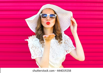 Fashion portrait pretty woman in summer straw hat sends an air kiss over colorful pink background