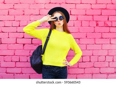 Fashion portrait pretty woman wearing a black hat and yellow knitted sweater over colorful pink bricks background