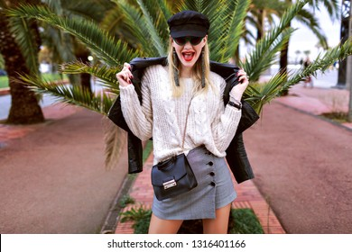 Fashion portrait of pretty young blithesome woman wearing stylish outfit, cap, leather jacket, cross body bag, mini skirt, sweater and trendy accessories and jewelry, spring time, Barcelona palm trees