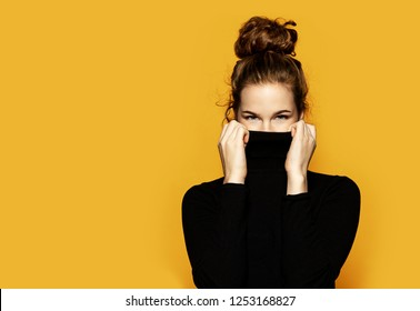 Fashion portrait of pretty young female dressed in fashionable black sweater standing on yellow background. Sweet brunette model trying to warm up. Lifestyle and trend concept