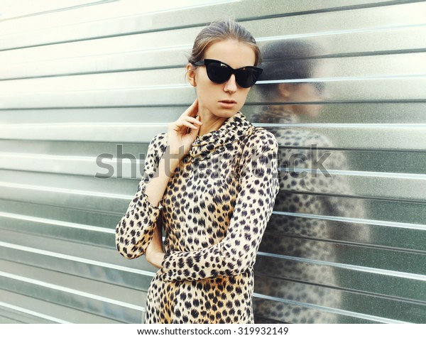 Fashion portrait pretty young woman wearing a sunglasses and leopard dress in the city
