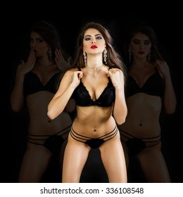 Fashion portrait of a professional model in black sexy underwear, isolated on dark background