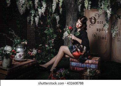 Fashion portrait of romantic beautiful girl with hairstyle, red lips, art dress, holding rose flower, sitting on books. Princess in mistery forest. Creative concept Once upon a time in fantasy.