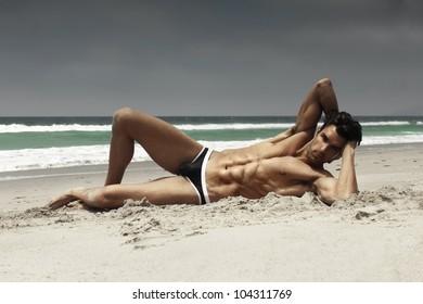 Fashion portrait of a sensual gorgeous male model in swimwear posing on beach