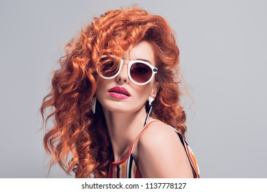 Fashion Portrait Sensual Redhead Girl with Trendy Wavy Curly Hairstyle in Studio. Beautiful woman in Stylish Summer Sunglasses. Close up female Face. Attractive Model on Purple