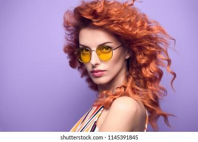 Fashion Portrait Sensual Redhead Girl with Shiny Wavy Curly Hairstyle in Studio. Beautiful woman in Stylish Summer Sunglasses. Attractive Playful Model on Purple