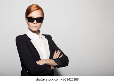 Fashion portrait of serious woman dressed as a secret agent or spy. Gray background.