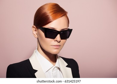 Fashion portrait of serious woman dressed as a secret agent or spy. Pink background.