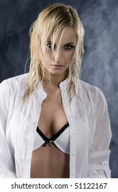 fashion portrait of a sexy blond girl in white shirt showing her bra on dark background with light effect
