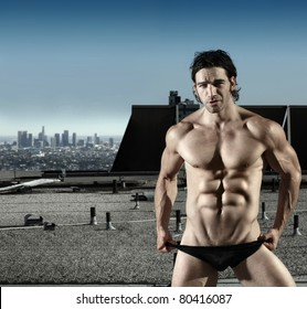 Fashion portrait of sexy male model in black briefs on top of roof with city in background