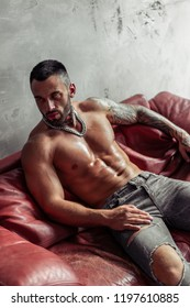 Fashion portrait of Sexy naked male model with tattoo and a black beard sitting in hot pose on red leather sofa. Loft room interior with grey concrete wall. Professional Studio image.
