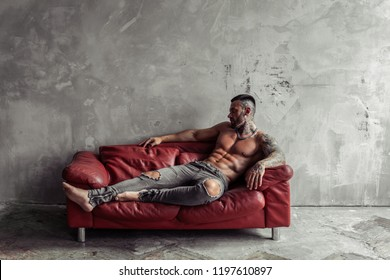 Fashion portrait of Sexy naked male model with tattoo and a black beard lying in hot pose on red leather sofa. Loft room interior with grey concrete wall. Professional Studio image.