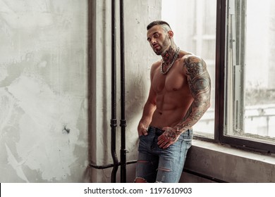 Fashion portrait of Sexy naked male model with tattoo and a black beard standing in hot pose on near the window. Loft room interior with grey concrete wall. Professional Studio image.