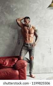 Fashion portrait of Sexy naked male model with tattoo and a black beard standing in hot pose on red leather sofa. Loft room interior with grey concrete wall. Professional Studio image.