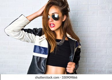 Fashion portrait of sexy stunning hipster woman, bright make up, vintage sunglasses, biker leather jacket, trendy jewelry and accessorizes. Urban wall background.