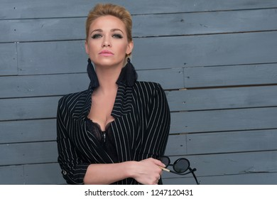 Fashion portrait of sexy woman in black jacket on blue wooden background