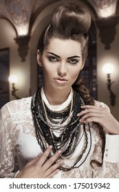 fashion portrait of sexy young brunette woman with amazing creative style, original hair-style and pretty make-up. Wearing white lace shirt and a lot of necklaces