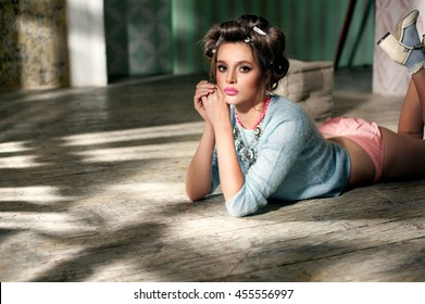 fashion portrait of sexy young housewife wearing hair rollers  posing on the wooden floor
