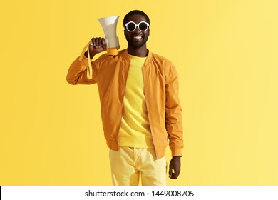Fashion portrait of smiling black man with megaphone on yellow background. Happy young african american male model in stylish sunglasses with loud speaker in studio