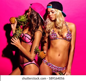 fashion portrait of smiling brunette and blond models in summer swimwear clothes on colorful pink background with fresh small baby pineapple