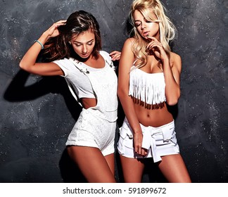 fashion portrait of smiling brunette and blond models in summer casual white clothes posing near gray dark wall