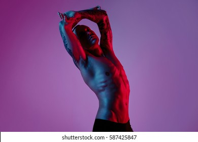 Fashion portrait of sport fit attractive man making arm stretch. Masculine naked body, tattooed hands, hipster look. ?olour flash studio light