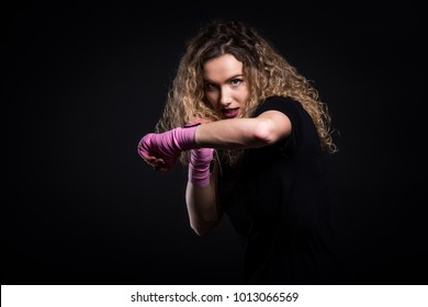 Fashion portrait of strong active kick boxing woman training. Attractive fit female is training martial arts and self defence for women. Shadow boxing with pink hand wraps isolated on balck background