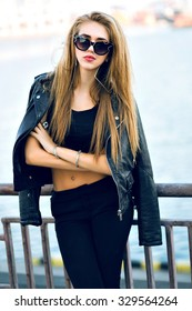 Fashion portrait of stunning sexy blonde woman, wearing brutal total black outfit, sunglasses, leather jacket, long hairs, vintage toned film colors, windy cold weather, autumn time, urban style.