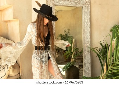 Fashion portrait stylish brunette woman in boho style, a girl in a stylish bohemian chic interior