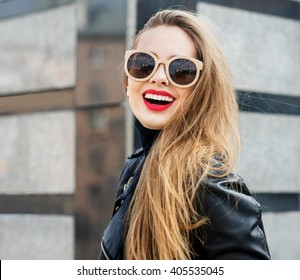 Fashion portrait stylish pretty woman in sunglasses outdoor. Young smiling woman wearing a rock black style having fun in city. Street fashion. Red lipstick.