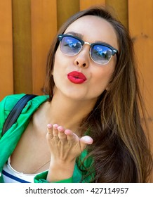 Fashion portrait stylish pretty woman in sunglasses posing in the city in a green jacket . Street fashion Beautiful Young Woman Outdoors. Blowing lips kiss.