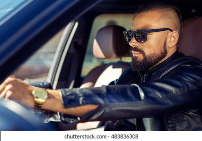 Fashion portrait of stylish young man in the car