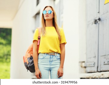 Fashion portrait trendy young woman wearing a sunglasses and t-shirt with backpack in the city