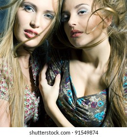 Fashion portrait of two beautiful women with streaming hair looking in camera