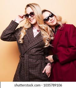 fashion portrait of two girls, best friends posing indoor on beige background wearing winter stylish coat.