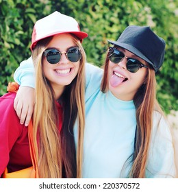 Fashion portrait of two pretty girls, wearing sweatshirt swag hats and sunglasses, having long blonde hairs outdoors on sunny summer day. Modern lifestyle concept. Photo toned style Instagram filters.