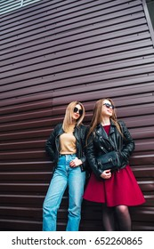 Fashion portrait of two  pretty women in black rock style in sunglasses over gray background in city .Two lovely young women talking and telling secrets
