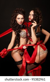 fashion portrait of two sexy brunette girls in light lingerie with long curly hair and jewelery bright makeup red lips with red ribbon isolated on black with headphones