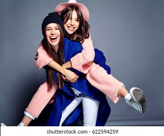 fashion portrait of two smiling brunette women models in summer casual hipster overcoat posing on gray background. Girls holding each other on back