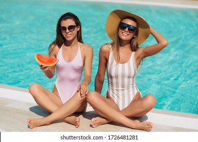 Fashion portrait of two stunning sexy girls laying near pool, amazing long blonde and brunette hair, stylish bikinis, pretty faces tanned slim body,eating watermelon , vacation