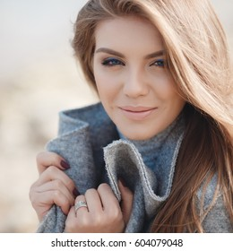 fashion portrait. woman in coat walking at coast and looking in camera. Emotive portrait of a fashionable model in white coat and beret posing at the winter seaside. Sunny weather. Outdoor