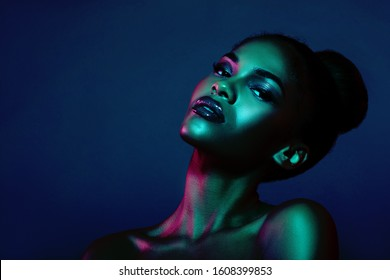 Fashion Portrait of a Woman with creative lighting and Beautiful Makeup. Blue Background. Black Girl in Blue Light. trendy color background