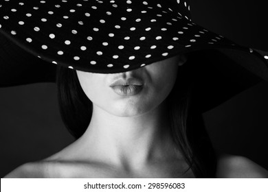 Fashion portrait of a woman with lock hair and  black and white dots hat and pout lips