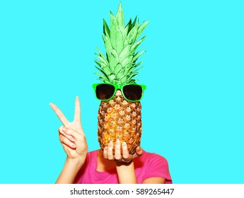 Fashion portrait woman and pineapple with sunglasses hiding head over blue background